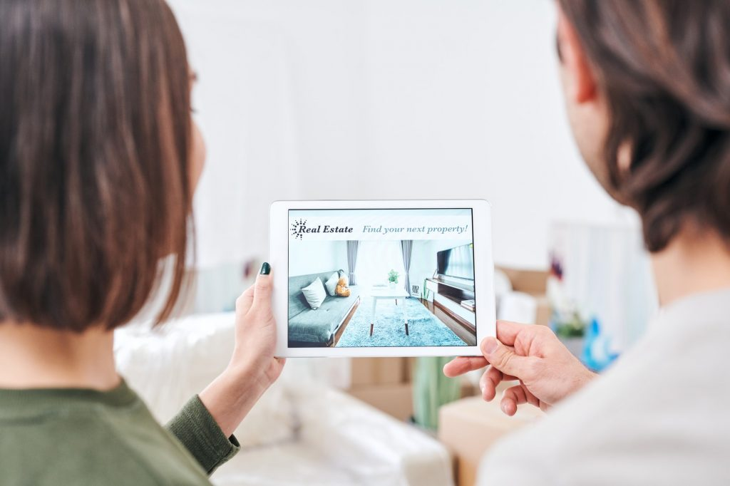 Young couple holding tablet with advertisement of real estate on sale